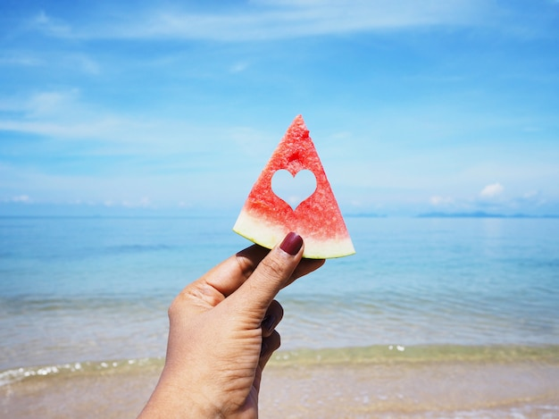 Anguria della holding della mano di selfie sopra la spiaggia di estate