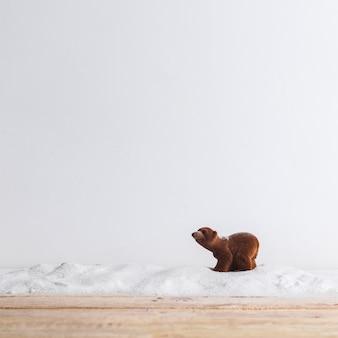 Animale giocattolo vicino a tavola di legno e mucchio di neve