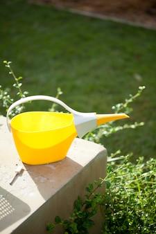 Annaffiatoio di plastica giallo in giardino