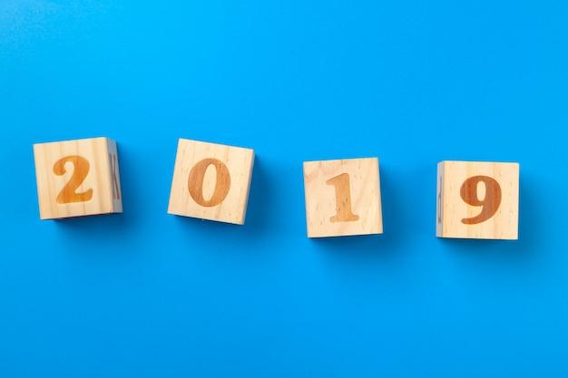 Anno 2019. blocchi alfabeto in legno colorato su sfondo blu, piatto laico, vista dall'alto.