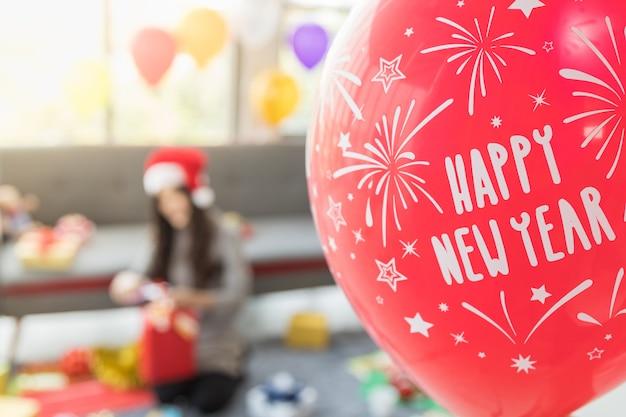 Anno nuovo e concetto di vacanza. la fine del pallone rosso e sfuocato della donna asiatica fa un contenitore di regalo e decora il salone per il partito.