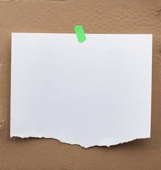 Annuncio di carta bianca con bordi strappati fissati con un velcro verde su una superficie di cartone marrone