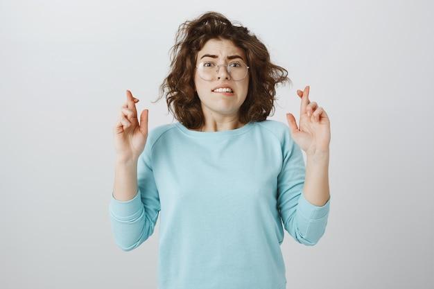 Ansiosa ragazza speranzosa incrocia le dita buona fortuna, esprimendo desideri o aspettando risultati