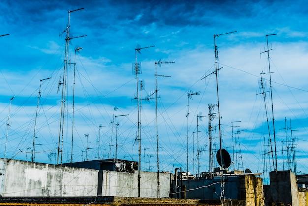 Antenne televisive sul tetto di un vecchio edificio con cielo drammatico.