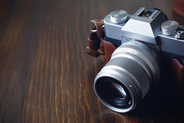 Antica macchina fotografica argento e nera con cinturino in pelle marrone sul tavolo di legno.