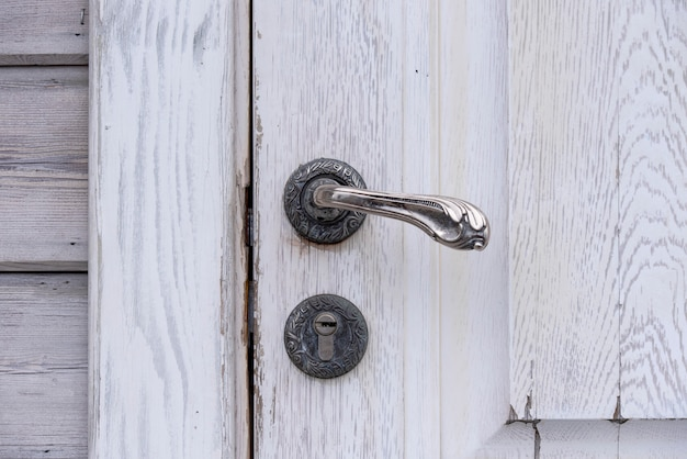 Antica vecchia porta di legno grigio vintage con manico in ferro e buco della serratura