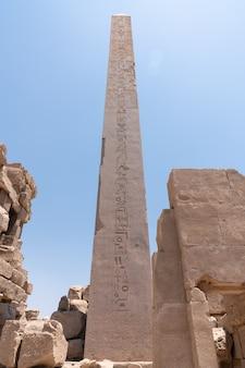 Antiche rovine del tempio di karnak in egitto in estate, obelix e statue di ramesse ii al primo pilone del tempio di luxor (1279-1213 a.c.)