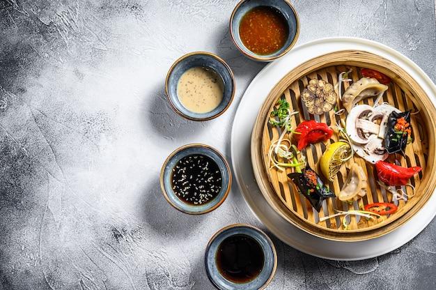 Antipasti assortiti di dim sum in un piroscafo di bambù. set di cibo cinese. sfondo grigio. vista dall'alto. copia spazio