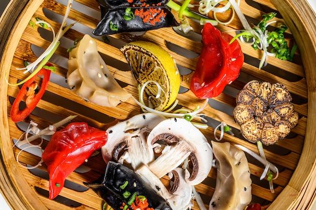 Antipasti assortiti di dim sum in un piroscafo di bambù. set di cibo cinese. sfondo grigio. vista dall'alto