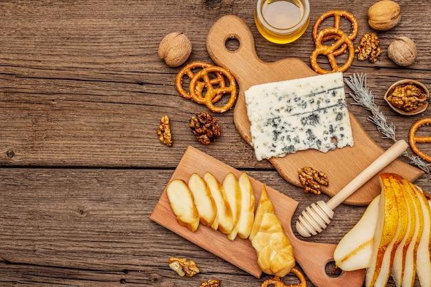 Antipasti di formaggi con formaggio affumicato e erborinato, cracker, miele, noci e pera matura. ricetta spuntino tradizionale