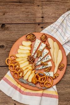 Antipasti di formaggi con formaggio affumicato e erborinato, cracker, miele, noci e pera matura.