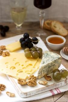 Antipasti di vari tipi di formaggio, uva, noci e miele, serviti con vino bianco e rosso