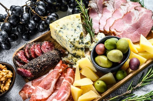 Antipasti italiani o antipasti set di specialità gastronomiche miste di formaggi e snack di carne. sfondo grigio. vista dall'alto