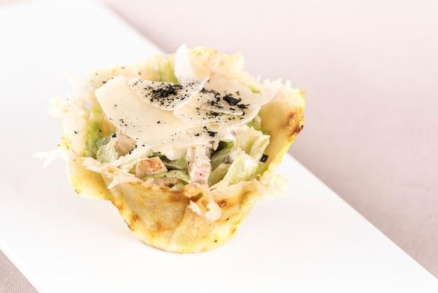 Antipasto con insalata caeser e filetto di pollo, servito in un cestino di parmigiano, piatto bianco