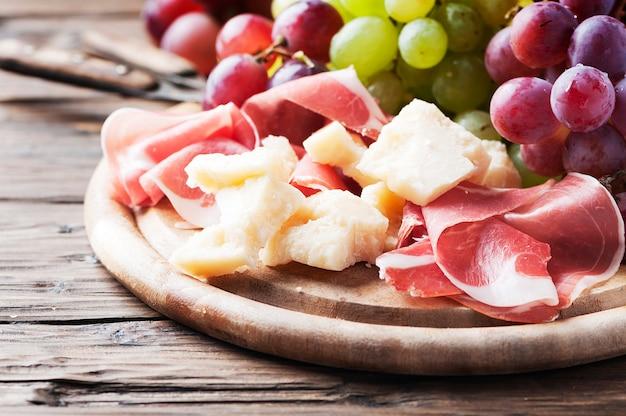 Antipasto con uva, formaggio e prosciutto