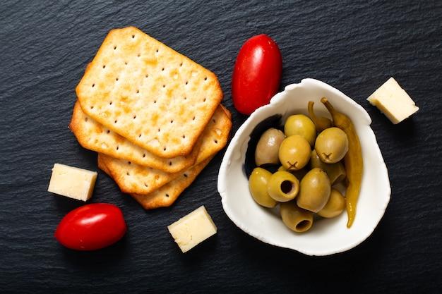 Antipasto di cibo olive formaggio, pomodori e cracker sul bordo di ardesia nera