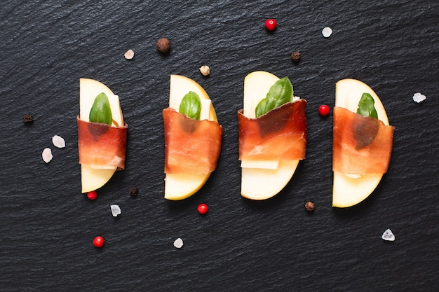 Antipasto di festa di cibo bresaola di manzo alla mela, brie e secca bresaola su lastra di ardesia nera