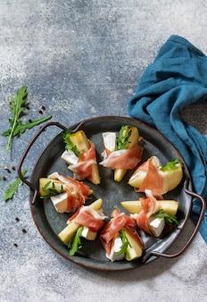 Antipasto di pere con prosciutto prosciutto, rucola e brie su un tavolo in pietra chiara copia spazio.