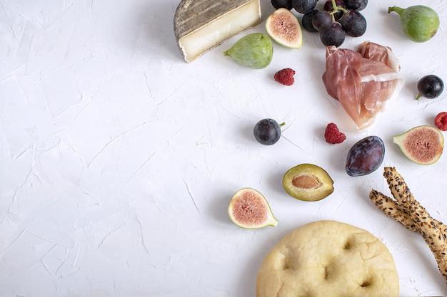 Antipasto di vino fico, uva, prugne, formaggio, focaccia, grissini