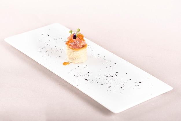Antipasto fresco con salmone affumicato e caviale, su pasta sfoglia, fiore viola commestibile