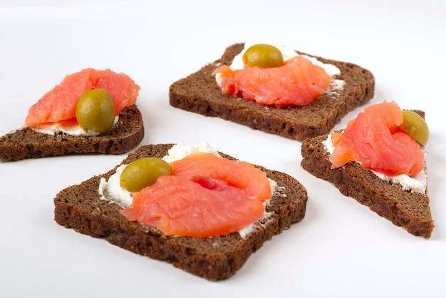 Antipasto, panino aperto con salmone e formaggio a pasta molle su fondo bianco. cucina tradizionale italiana o scandinava. concetto di corretta alimentazione e alimentazione sana