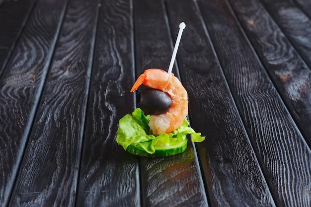Antipasto per la ricezione. fetta di cetriolo con gamberi e olive sullo spiedo