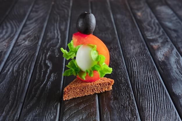 Antipasto per la ricezione. pane nero con uovo di quaglia, pomodoro, foglia di insalata e olive su spiedino