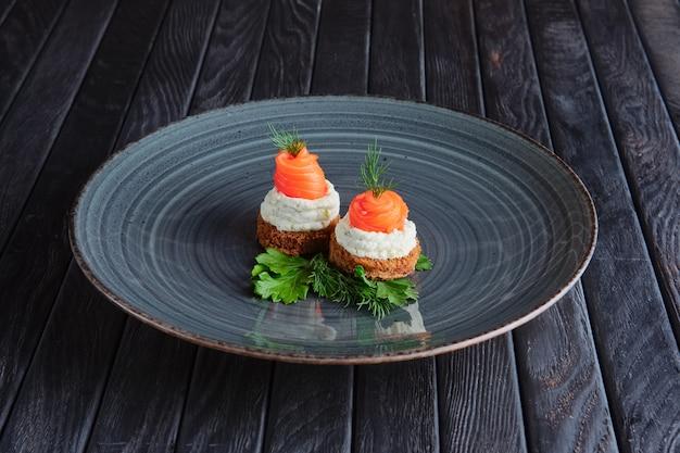 Antipasto per la ricezione. salmone affumicato con ricotta e aneto su un pezzo di pane integrale