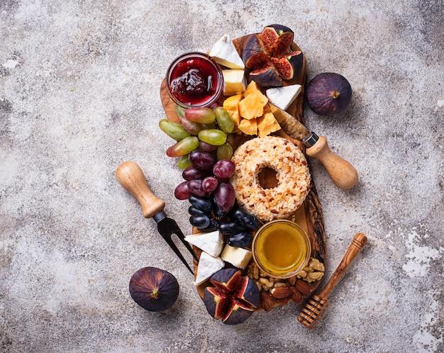 Antipasto per vino, piatto di formaggi con uva e fichi