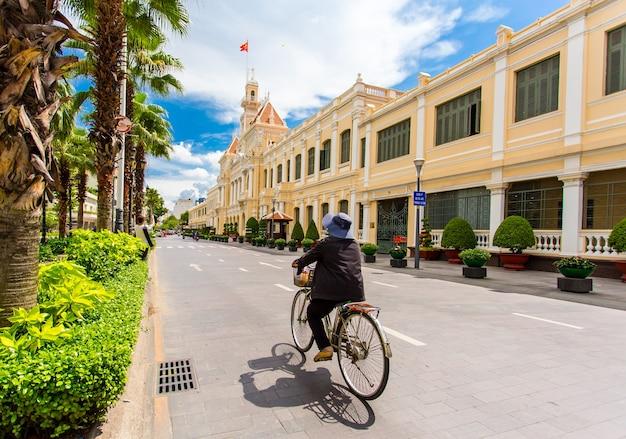 Anziana che sbarazza bicicletta sulla strada nella parte anteriore di ho chi minh city hall
