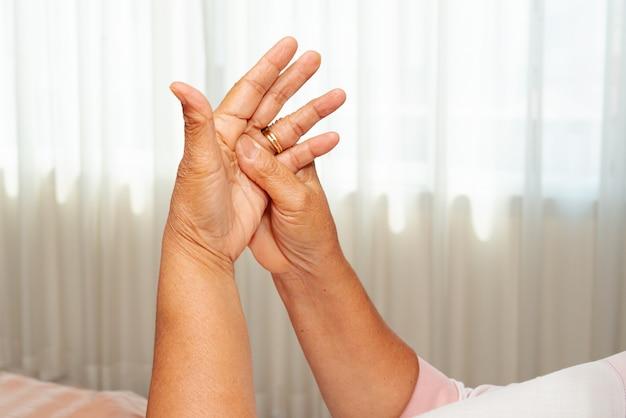 Anziana che soffre dal dolore della mano del polso, concetto di problema sanitario