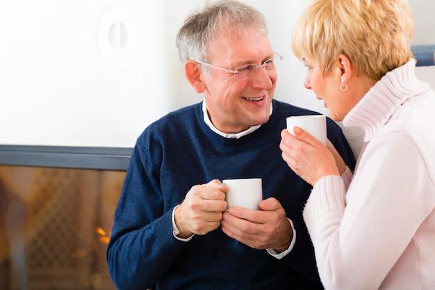 Anziani a casa davanti al camino con una tazza di tè