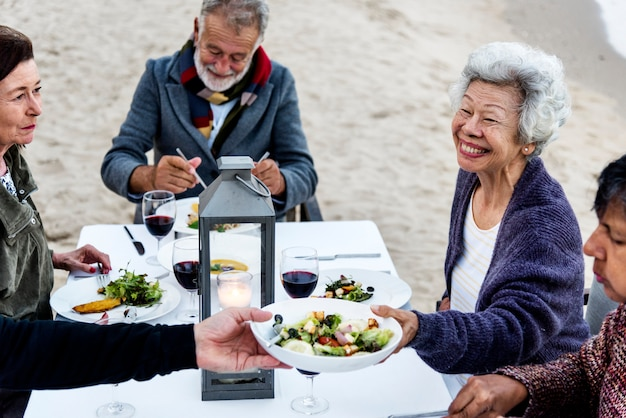 Anziani che hanno una cena in spiaggia