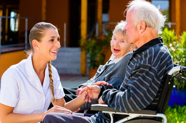 Anziani che mangiano caramelle nel giardino della casa di cura