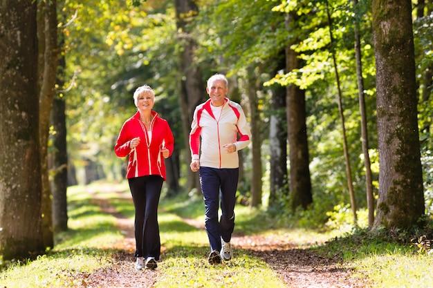 Anziani che pareggiano su un sentiero forestale