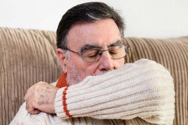 Anziani che starnutiscono, tossiscono nella manica o nel gomito per prevenire la diffusione di covid-19.