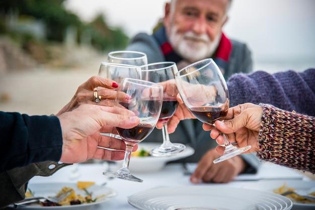 Anziani che tostano con vino rosso in spiaggia