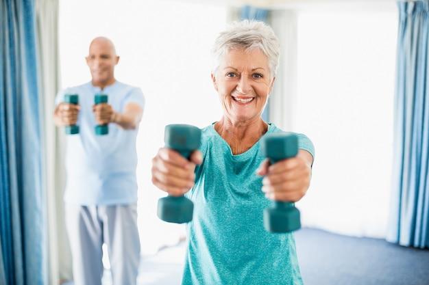 Anziani che usano i pesi