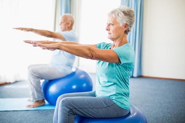 Anziani che usano la palla di esercizio
