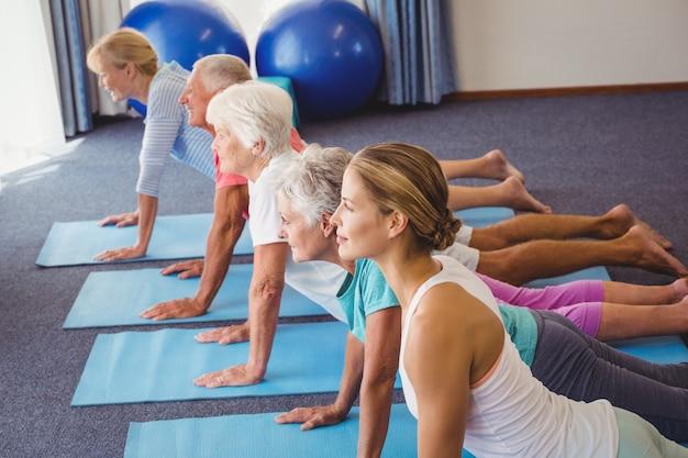 Anziani e istruttore di fitness che allungano le gambe