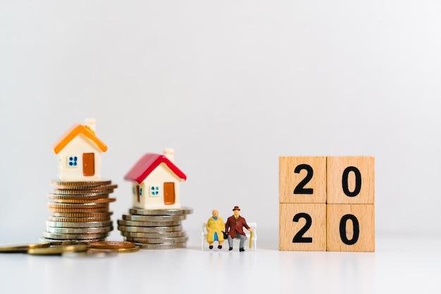 Anziani in miniatura che si siedono con il blocco di legno 2020 e le mini case sulla pila di monete