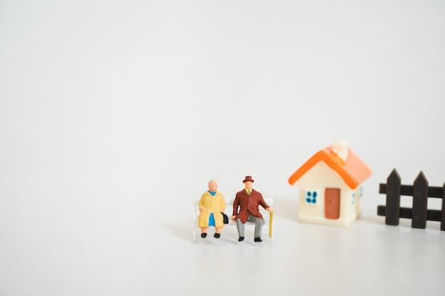 Anziani in miniatura che si siedono mini casa usando come pensione di lavoro e concetto di famiglia