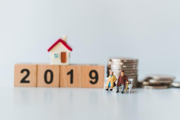 Anziani in miniatura delle coppie che si siedono sull'anno di legno 2019 e sulle monete della pila