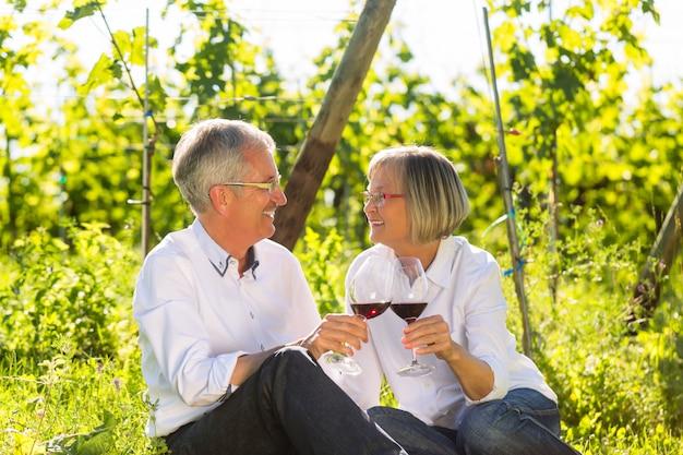 Anziani seduti in vigna bevendo vino rosso