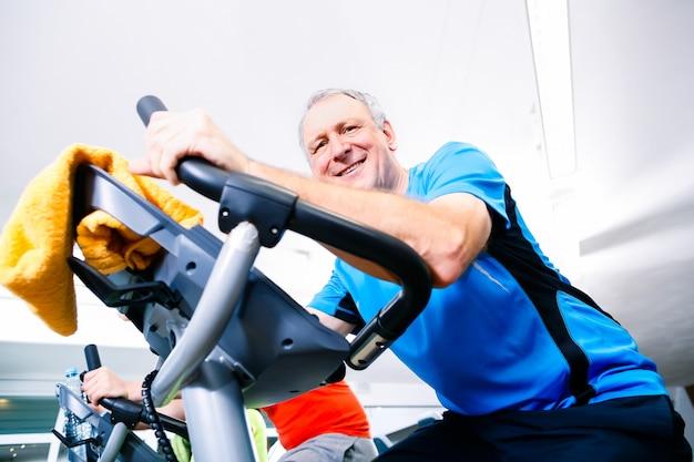 Anziano che fa sport sulla bici di filatura in palestra