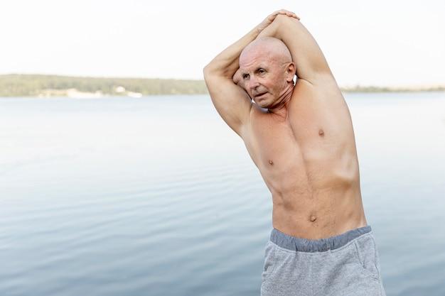 Anziano che lavora vicino al lago