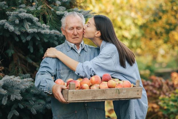 Anziano che sta in un giardino di estate con il raccolto