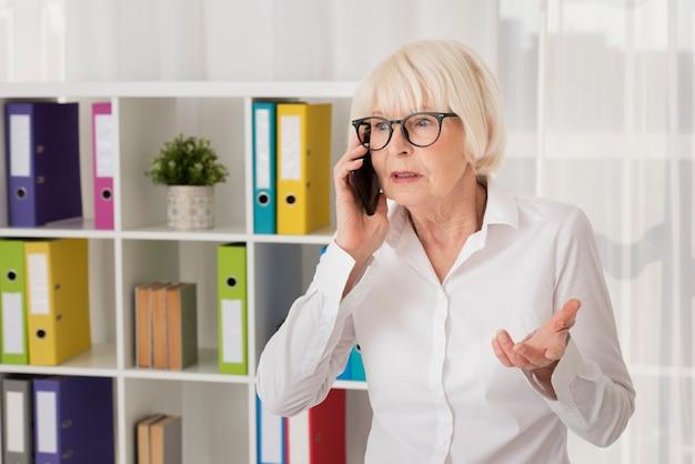 Anziano con gli occhiali che parla al telefono