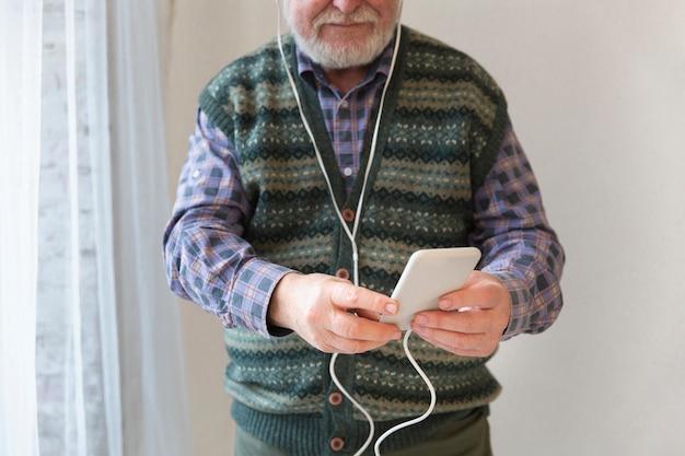Anziano del primo piano che gioca musica sul cellulare