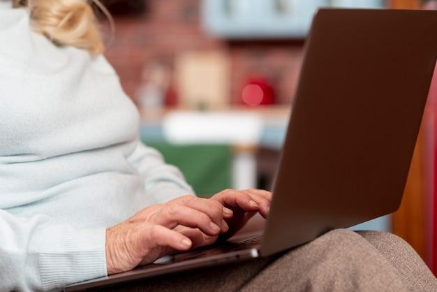 Anziano del primo piano che per mezzo del computer portatile a casa